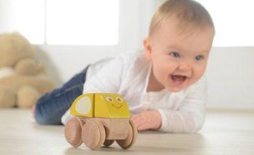 бебе си играе с дървена играчка